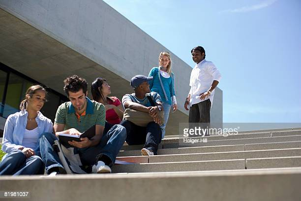 University students studying and socializing on stairs on campus
