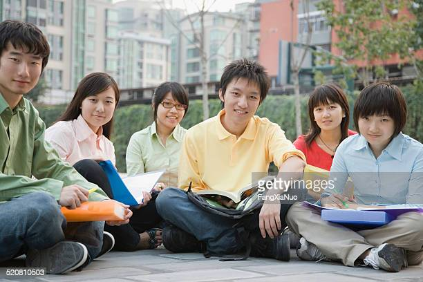 University students with sitting with holding book, smiling, portrait