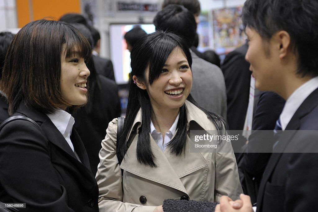 University students Yurika Nakazawa, left, and Kana Misonou, center, speak to a recruiter at a job fair hosted by Mynavi Corp. in Tokyo, Japan, on Saturday, Dec. 8, 2012. In Japan, many students accept job offers from large companies six months before graduating and may stay with the same employer until retirement, said Yoshihide Suzuki, an administrative director at the career center at Waseda University. Photographer: Akio Kon/Bloomberg via Getty Images