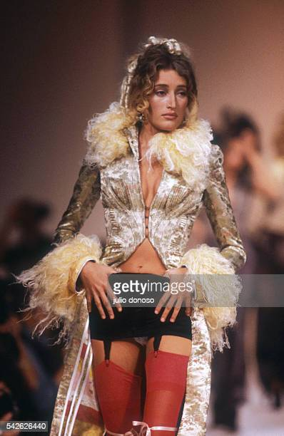 Unkempt fur cuffs and collar adorn a long coat in designer Chantal Thomass' 1992 SpringSummer ReadytoWear collection A black miniskirt and red...