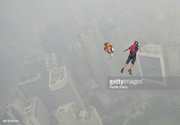 Unknown base jumpers leap from a high open deck on the Kuala Lumpur Tower in hazy conditions during the international tower jump