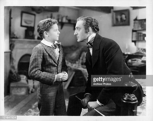 Unknown child actor and Basil Rathbone face to face in a scene from the film 'Anna Karenina' 1935