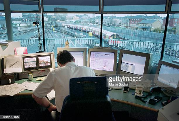 Unknown man sitting at desk in London Underground control room with computer monitors showing train details with tracks and tube train visible...