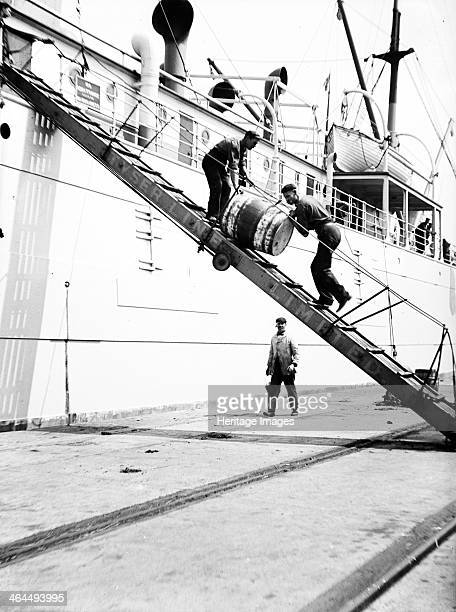 Unloading a barrel from a ship down a gangway London c1905