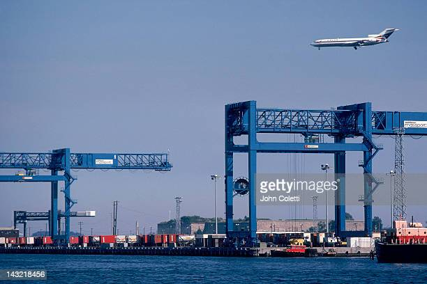 Unloading docks w/ plane in sky, south Boston, MA
