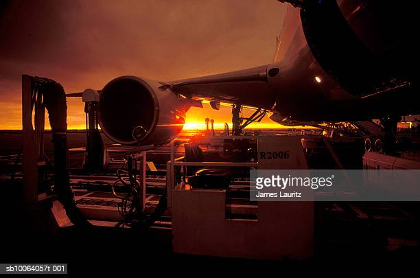 Unloading of airplane at sunset