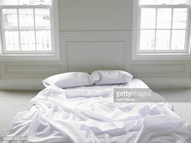 Unmade bed on floor, elevated view