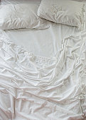 Unmade bed with white sheets