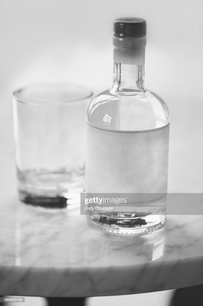 Unmarked sealed bottle and glass on table