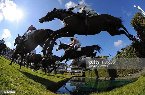Unowatimeen ridden by Samantha Drake jumps the water jump during the Fox Hunters Steeple chase during the first day of the Grand National horse...