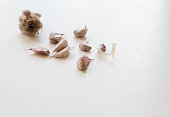 Unpeeled garlic cloves on white table (selective focus)