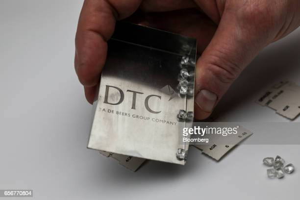 Unpolished diamonds sit on a shovel scoop at the De Beers SA headquarters on Charterhouse Street in London UK on Wednesday Feb 1 2017 Number 17...