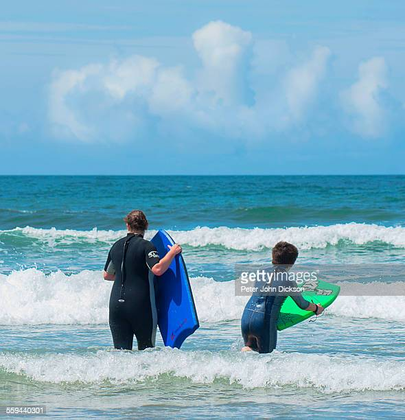 Unrecognisable people are standing in the ocean with body boards waiting for a wave to break in Croyde Devonshire UK June 2012