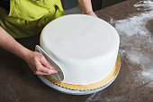 Unrecognisable woman in bakery decorating wedding cake with white fondant