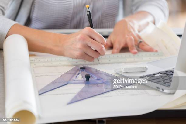 Unrecognizable architect uses tools while working on plans