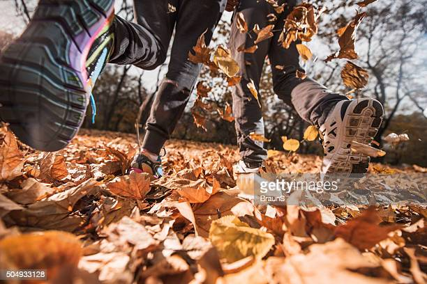 Unrecognizable athletes running on autumn leaves in nature.