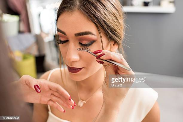Unrecognizable beautician applying false eyelash in beauty salon.