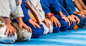 Group of unrecognizable children martial artist in a row on a karate training.