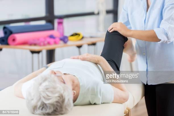 Unrecognizable chiropractor works on senior woman's knee