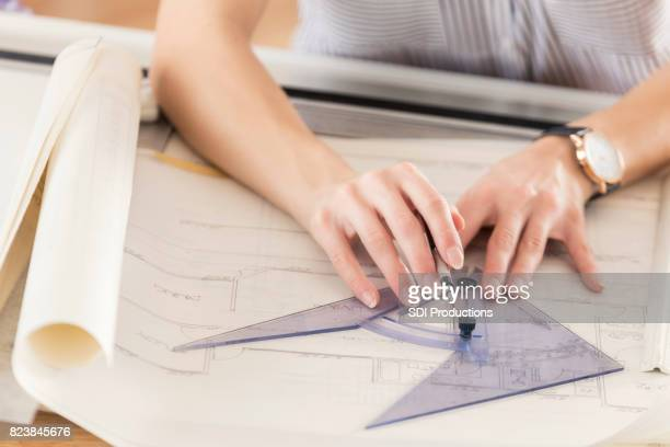 Unrecognizable female architect draws blueprint with protractor