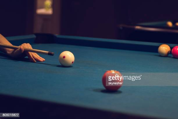 Unrecognizable female person aiming at pool ball during snooker game.