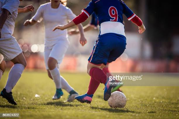 Unrecognizable female soccer players tackling on playing field.