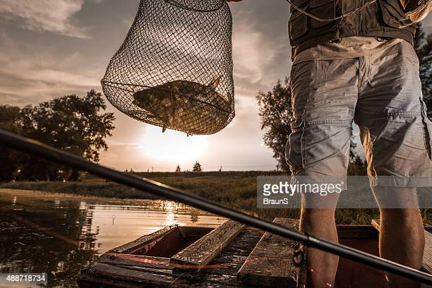 Unrecognizable fisherman caught a common carp in a fish cage.