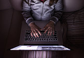 Unrecognizable girl, sitting in a dark, playing with laptop. Child at home, sitting on sofa.