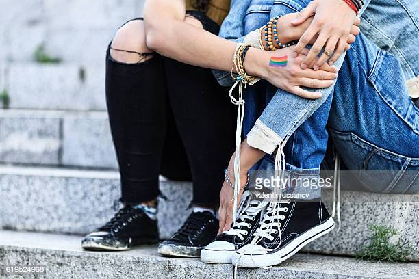 Unrecognizable girls embracing and sitting on stairs