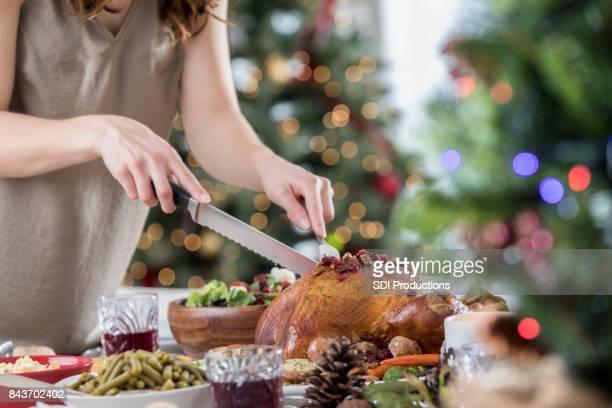 Unrecognizable hostess carves Christmas turkey before dinner