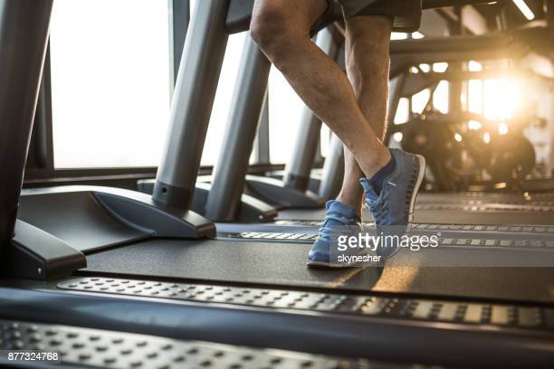 Unrecognizable male athlete standing on treadmill in a gym.