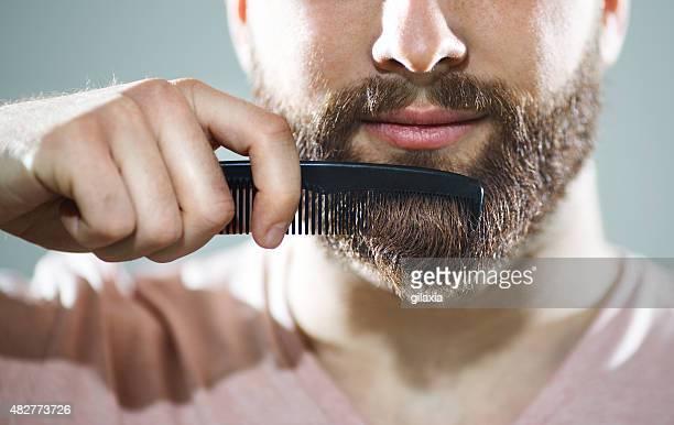 Hombre irreconocible peinar su barba