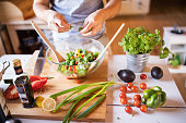 Unrecognizable man cooking. A man making vegetable salad.