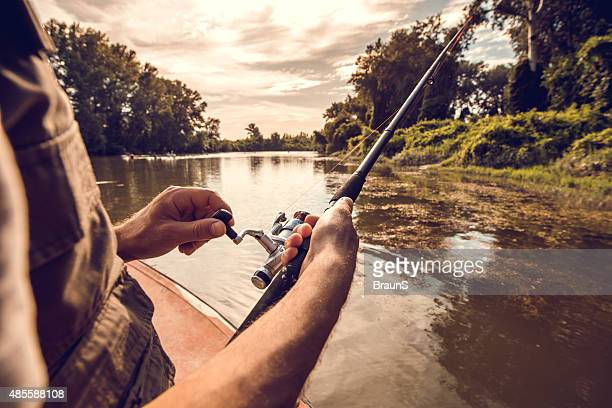 Unrecognizable man fly-fishing on the river.