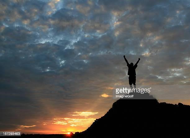 Nicht erkennbare Mann auf Berggipfel mit Arme hoch