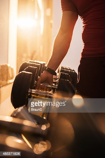 Unrecognizable man taking dumbbell from a rack at gym.