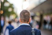 Head of unrecognizable manager walking in the street of London, back view