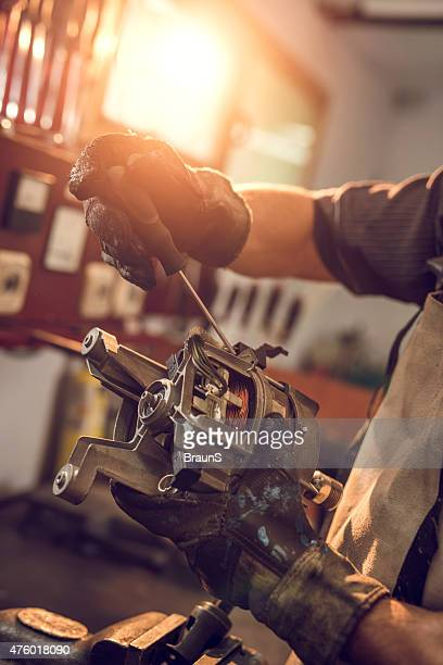 Unrecognizable manual worker working on electric motor.