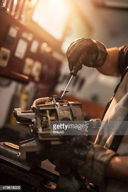 Operaio manuale irriconoscibile lavoro motore elettrico.