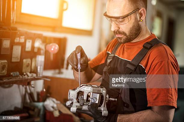 Unrecognizable manual worker working on electric motor