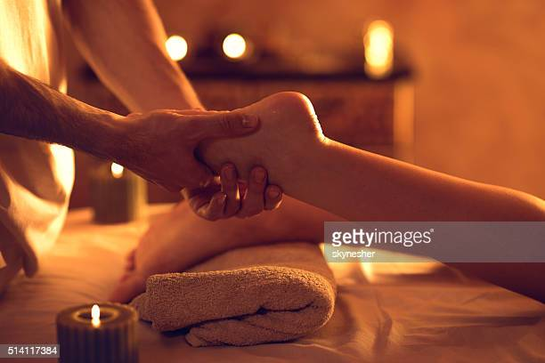 Unrecognizable massage therapist massaging woman's foot at spa.