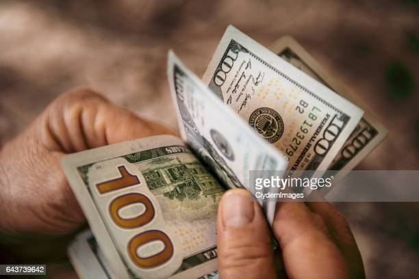Unrecognizable mature man counting USA Dollar bills