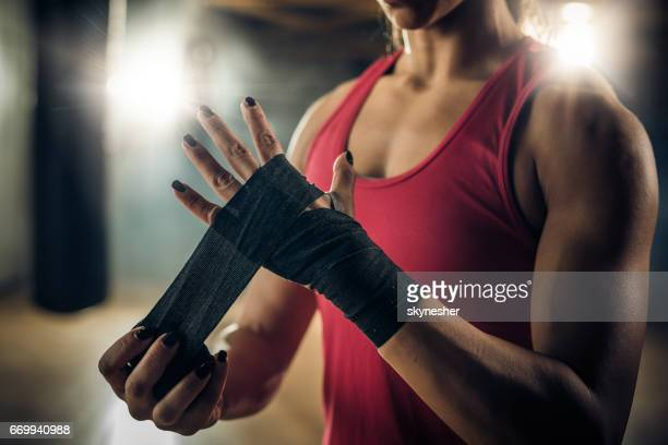 Unrecognizable muscular build woman wrapping her hand with a bandage before boxing training.