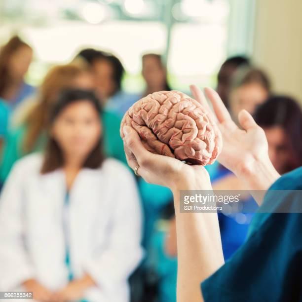 Unrecognizable neurologist teaches continuing education class