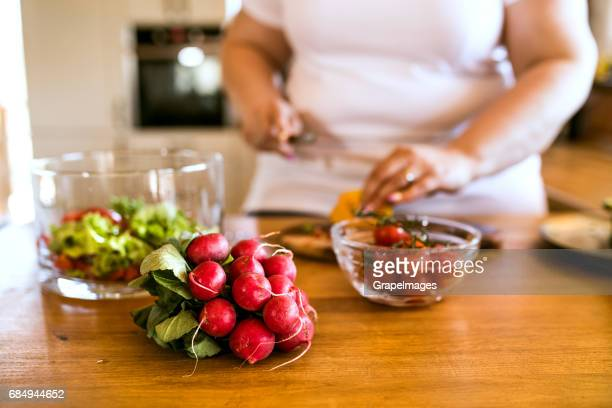 Unrecognizable overweight woman at home preparing a delicious healthy vegetable salad in her kitchen.