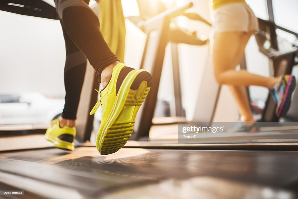 Unrecognizable people running on treadmills in a gym.