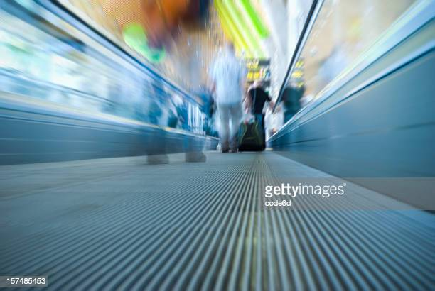 Unrecognizable people travelling, airport escalator, motion blur