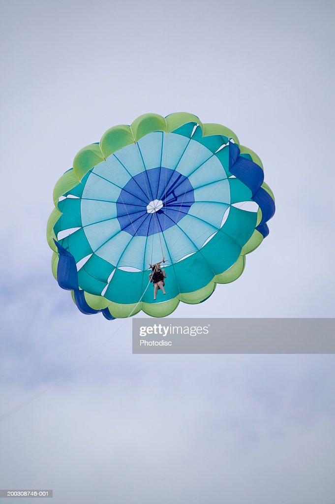 Unrecognizable person parachuting, view from below : Stock Photo