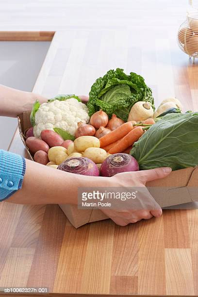 Unrecognizable person placing cardboard box with fresh vegetables on kitchen counter, close-up of hands