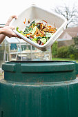 Unrecognizable person pouring kitchen waste into compost bin, close-up of hands